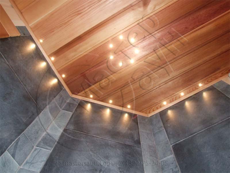 sauna-so-stenkoj-iz-dekorativnogo-kamnya-i-tochechnoj-podsvetkoj-pechki-8